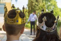Kleines M?dchen und ein Junge mit Kronen auf den K?pfen passen eine Leistung eines Magiers durch eine Geburtstagsfeier im Freien  lizenzfreies stockfoto