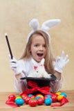 Kleines Magiermädchen, das Ostern-Einzelteile beschwört Stockfoto