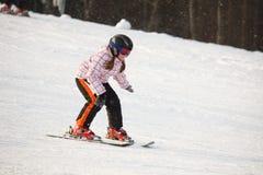 Kleines Mädchen, das alpines Skifahren erlernt Stockfotografie