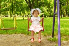 Kleines Mädchen, das auf dem Schwingen sitzt Stockfotos