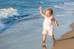 Kleines Mädchen, das auf dem Strand spielt Stockbilder