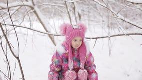 Kleines Mädchen, das auf den Niederlassungen von Bäumen, schneebedeckt schwingt stock footage
