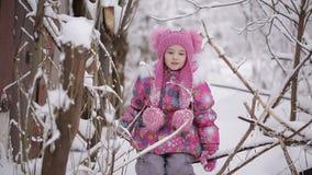 Kleines Mädchen, das auf den Niederlassungen von Bäumen, schneebedeckt schwingt stock video footage