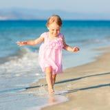 Kleines Mädchen, das auf den Strand läuft Stockfotos
