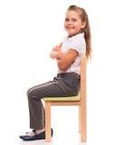 Kleines Mädchen, das auf einem Stuhl und einem Lächeln sitzt Lizenzfreie Stockfotos