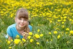 Kleines Mädchen, das auf Gras in der Blume liegt. Stockfoto