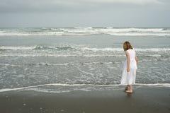 Kleines Mädchen, das auf Strand im weißen Kleid spielt Lizenzfreies Stockfoto