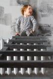 Kleines Mädchen, das auf Treppe sitzt und Gesichter macht Stockfotografie