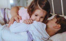 Kleines Mädchen, das über dem Jungen liegt im Bett spielt Lizenzfreie Stockbilder