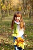 Kleines Mädchen, das Blätter schreit und anhält Stockbild