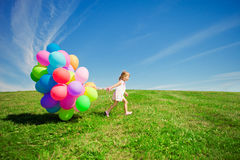 Kleines Mädchen, das bunte Ballone hält. Kind, das auf einem Grün spielt Stockfotos