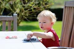 Kleines Mädchen, das draußen Blaubeeren isst Lizenzfreie Stockfotos