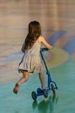 Kleines Mädchen, das draußen einen Roller reitet Stockfotografie