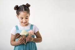 Kleines Mädchen, das drei Eiscremekegel anhält Stockfotografie