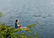 Kleines Mädchen, das durch den See meditiert Lizenzfreies Stockbild