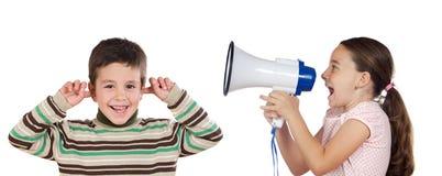 Kleines Mädchen, das durch Megaphon an einem Jungen schreit Lizenzfreie Stockfotografie