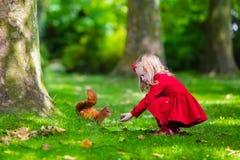 Kleines Mädchen, das ein Eichhörnchen im Herbstpark einzieht Stockfotografie