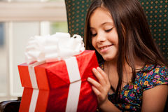 Kleines Mädchen, das eine Geschenkbox öffnet Stockbild