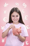 Kleines Mädchen, das eine Münze in ein Sparschwein einfügt Stockbilder