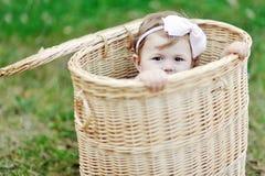 Kleines Mädchen, das in einem Korb sich versteckt Stockfotos