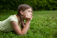 Kleines Mädchen, das in einem Park denkt Stockbilder