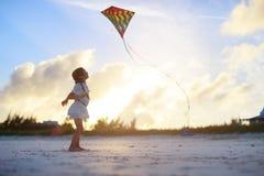 Kleines Mädchen, das einen Drachen fliegt Stockfotografie