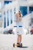 Kleines Mädchen, das einen Roller in der Stadt reitet Stockfotografie