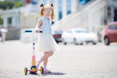 Kleines Mädchen, das einen Roller in der Stadt reitet Lizenzfreies Stockfoto
