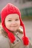 kleines Mädchen, das einen roten handgestrickten Hut trägt Stockfotografie