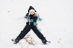 Kleines Mädchen, das ersten Schnee genießt Stockbild