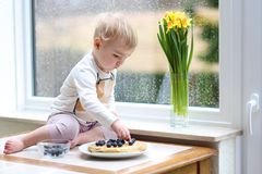 Kleines Mädchen, das geschmackvolle Pfannkuchen zuhause essen spielt Lizenzfreies Stockfoto
