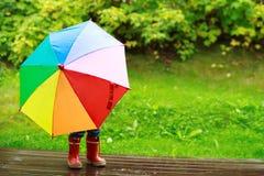 Kleines Mädchen, das hinter Regenschirm sich versteckt Lizenzfreies Stockfoto