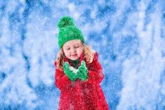 Kleines Mädchen, das im Park des verschneiten Winters spielt Stockfotos