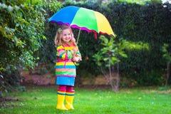Kleines Mädchen, das im Regen unter buntem Regenschirm spielt Stockbilder