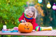 Kleines Mädchen, das Kürbis bei Halloween schnitzt Lizenzfreies Stockbild