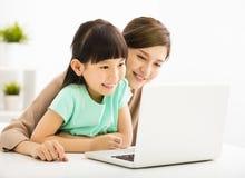 Kleines Mädchen, das Laptop mit ihrer Mutter betrachtet Stockbild