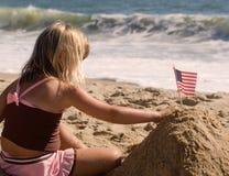 Kleines Mädchen, das Markierungsfahne im Sand pflanzt Lizenzfreie Stockbilder