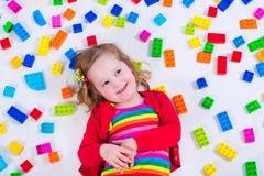 Kleines Mädchen, das mit bunten Blöcken spielt Lizenzfreie Stockfotos