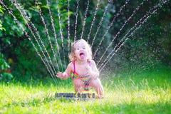 Kleines Mädchen, das mit Gartenberieselungsanlage spielt Stockbild