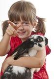 Kleines Mädchen, das mit ihrem Kaninchen spielt Stockbild