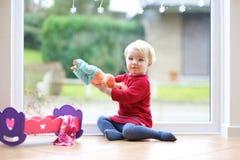 Kleines Mädchen, das mit ihrer Puppe spielt Stockbild