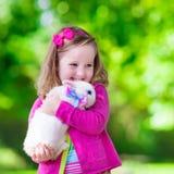 Kleines Mädchen, das mit Kaninchen spielt Lizenzfreie Stockfotos