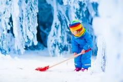 Kleines Mädchen, das mit Schnee im Winter spielt Lizenzfreie Stockfotografie
