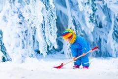 Kleines Mädchen, das mit Schnee im Winter spielt Lizenzfreie Stockbilder