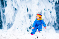 Kleines Mädchen, das mit Schnee im Winter spielt Lizenzfreies Stockbild