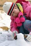 Kleines Mädchen, das mit Schnee spielt Lizenzfreies Stockfoto