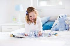 Kleines Mädchen, das mit Spielzeug spielt und ein Buch im Bett liest Lizenzfreie Stockfotos