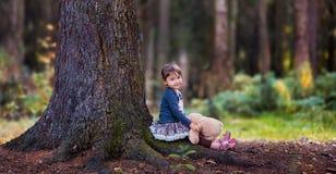 Kleines Mädchen, das mit Teddybären sitzt Stockfoto