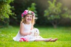 Kleines Mädchen, das mit wirklichem Kaninchen spielt Lizenzfreie Stockfotografie