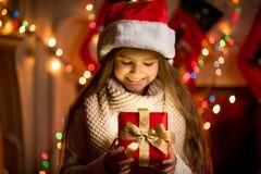 Kleines Mädchen, das offenen Kasten mit Weihnachtsgeschenk betrachtet Lizenzfreie Stockbilder
